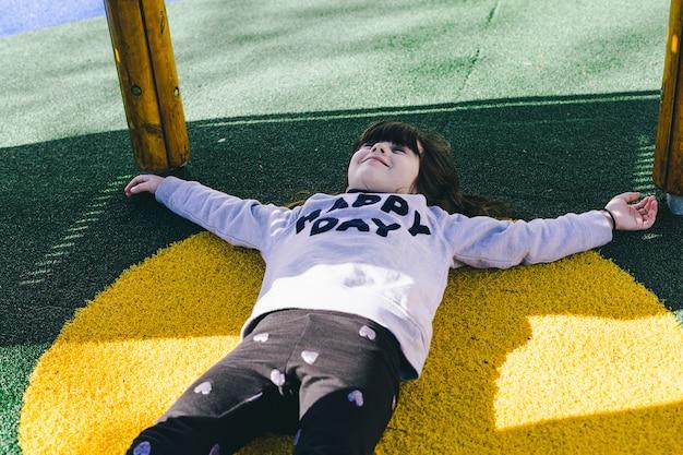 Jolie fille se trouvant sous aire de jeux Photo gratuit