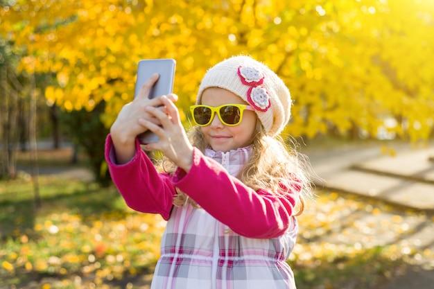 Jolie fille de sept ans faisant selfie à l'aide de smartphone Photo Premium