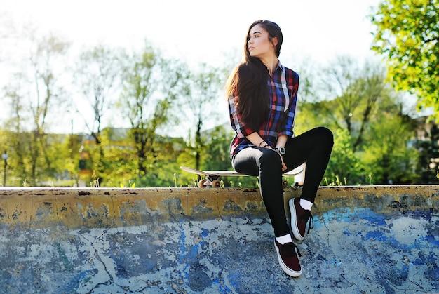 Jolie fille avec skateboard sur le fond du parc Photo Premium