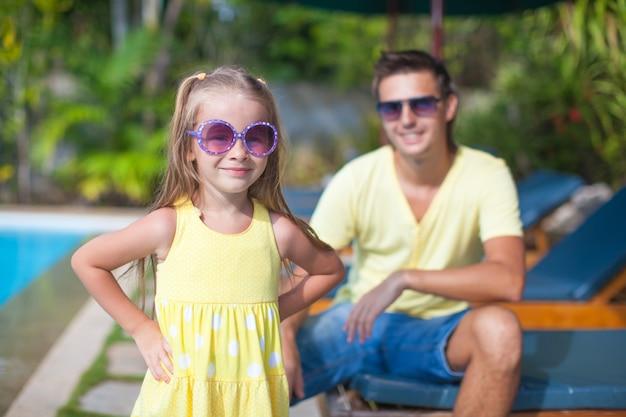 Jolie fille avec son jeune papa près de la piscine Photo Premium