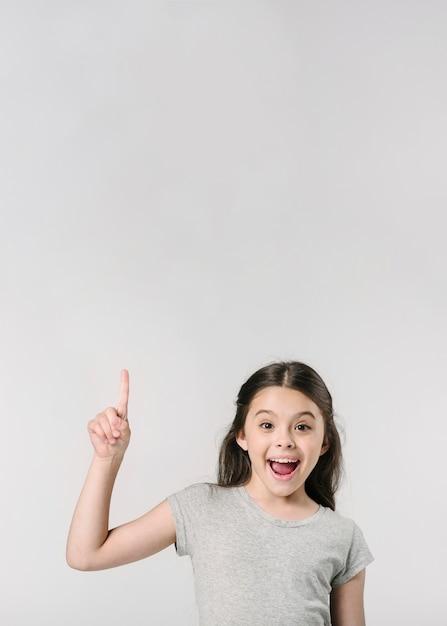 Jolie fille souriante avec le doigt en studio Photo gratuit