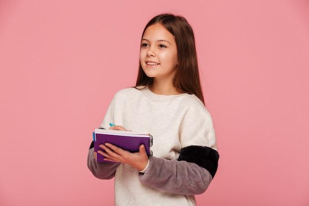 Jolie Fille Souriante Regardant De Côté Et écrit Dans Le Cahier Isolé Photo gratuit