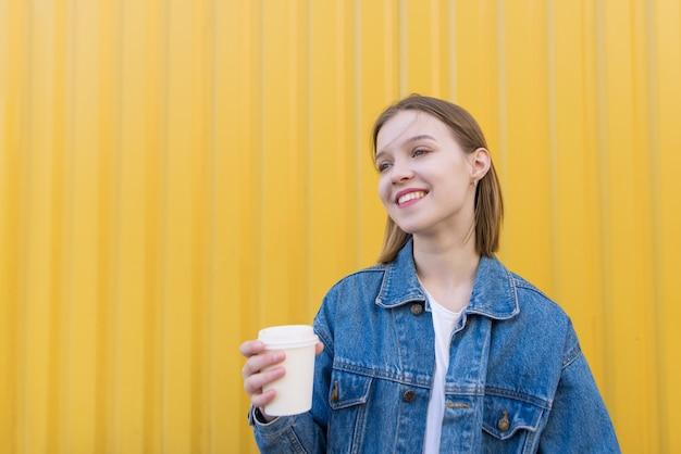 Une Jolie Fille Avec Une Tasse De Café Dans Ses Mains Se Dresse Sur Fond De Mur Jaune Et Sourit. Photo Premium