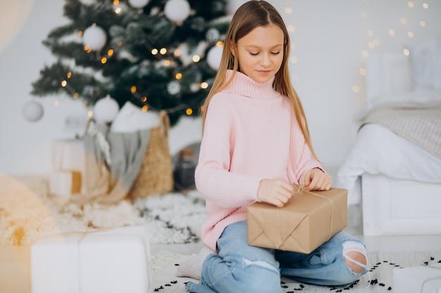 Jolie Fille Tenant Des Cadeaux De Noël Par Arbre De Noël Photo gratuit