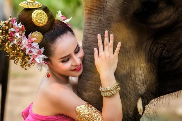 Jolie fille thaïlandaise en robe thaïlandaise traditionnelle avec éléphant Photo Premium