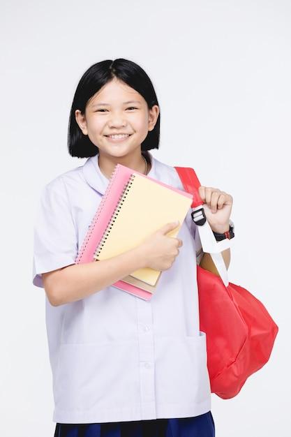 Jolie fille en uniforme d'étudiant avec papeterie sur gris Photo Premium