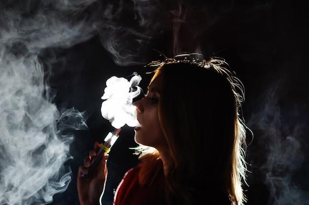 Jolie fille viper fumée e-cigarette dans une discothèque Photo Premium