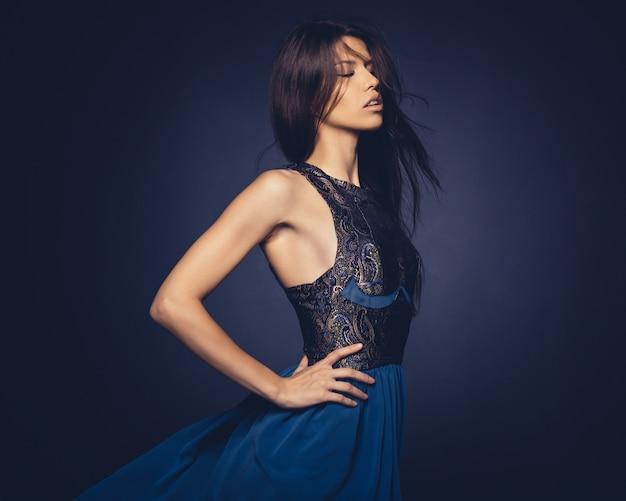 Jolie fille avec des volants de cheveux qui pose en studio Photo gratuit