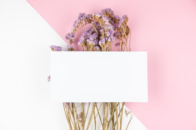 Jolie fleur de statice violette séchée avec une carte blanche sur le dessus Photo Premium