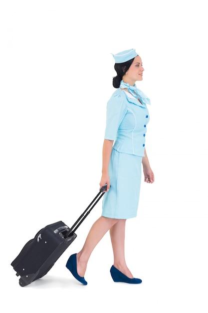 Jolie hôtesse de l'air à pied avec valise Photo Premium