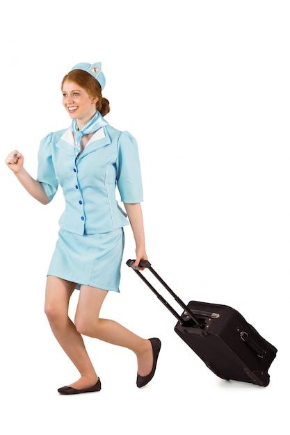 Jolie hôtesse de l'air tirant la valise Photo Premium