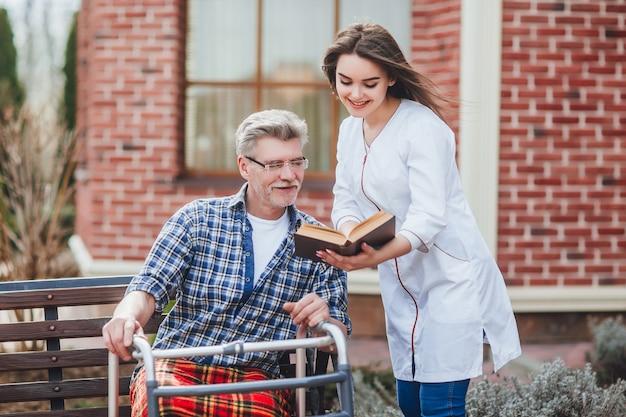 Jolie infirmière lisant un livre pour vieillard près de hispital Photo Premium