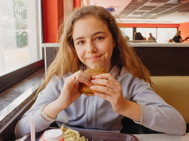 Jolie jeune adolescente avec un appétit en train de manger un hamburger dans un café Photo Premium