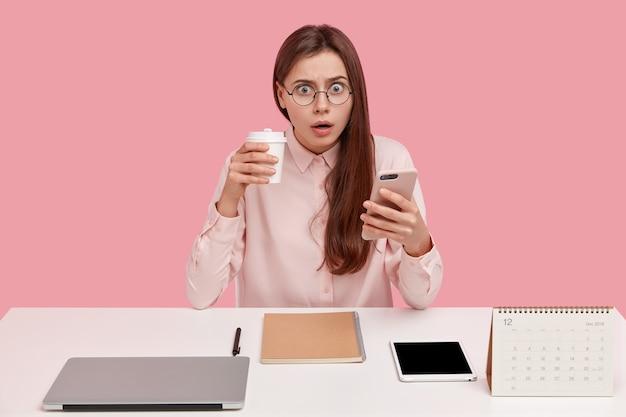 Une Jolie Jeune Blogueuse Brune Lit Une Notification Reçue Sur Un Cellulaire, A Surpris L'expression Photo gratuit
