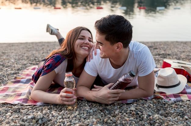 Jolie jeune couple s'amusant au bord du lac Photo gratuit