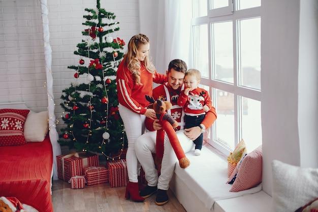 Jolie jeune famille assis à la maison Photo gratuit