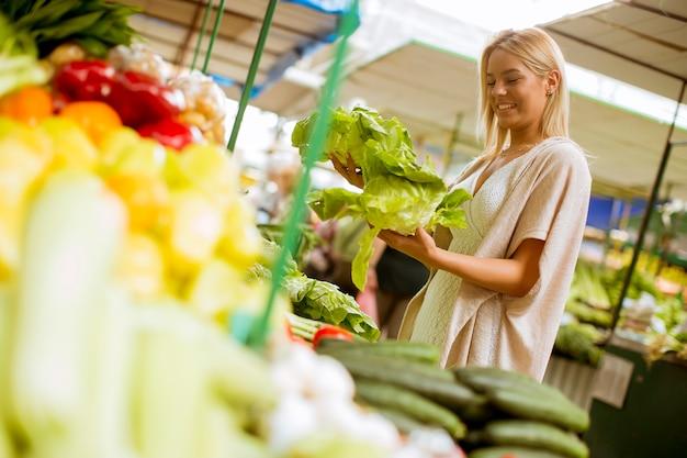 Jolie jeune femme achète des légumes au marché Photo Premium