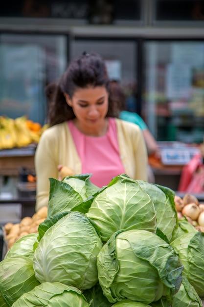 Jolie jeune femme achète des légumes sur le marché Photo Premium