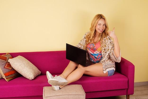 Jolie Jeune Femme à L'aide De Son Ordinateur Portable Tout En Vous Relaxant Photo Premium