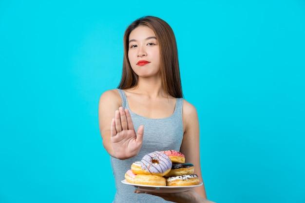 Jolie Jeune Femme Asiatique Ne Faisant Aucune Action Avec Des Beignets Sur Le Mur De Couleur Bleu Isolé Photo Premium