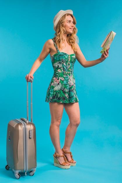 Jolie jeune femme au chapeau tenant la carte et la valise Photo gratuit