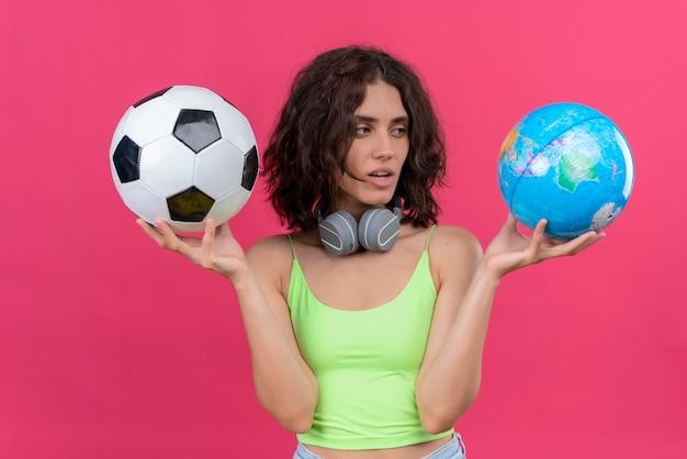 Une Jolie Jeune Femme Aux Cheveux Courts En Vert Crop Top Dans Les écouteurs Tenant Globe Et Ballon De Football Photo gratuit