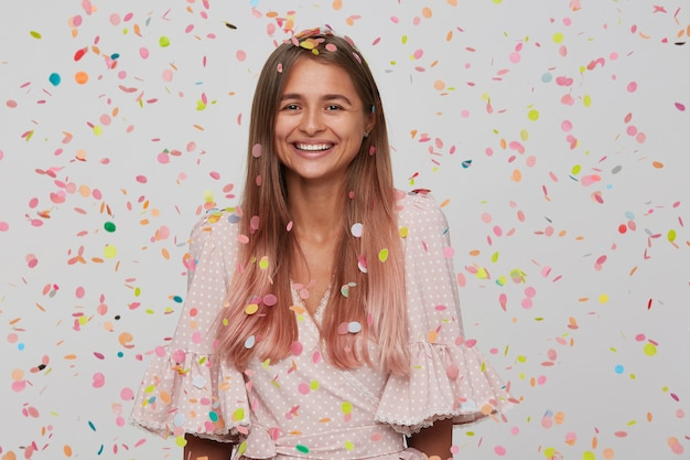 Jolie Jeune Femme Aux Cheveux Longs Et Bouche Ouverte Porte Une Robe Rose Avec Des Confettis Photo gratuit