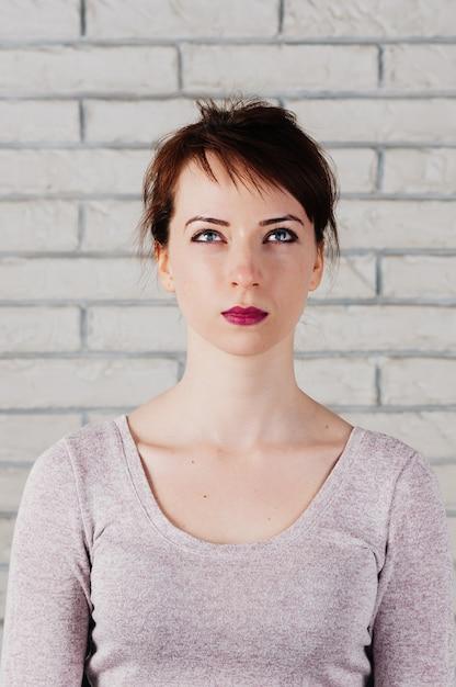 Jolie Jeune Femme Aux Yeux Plissés Et Regardant Vers Le Haut, La Bouche Fermée Photo Premium