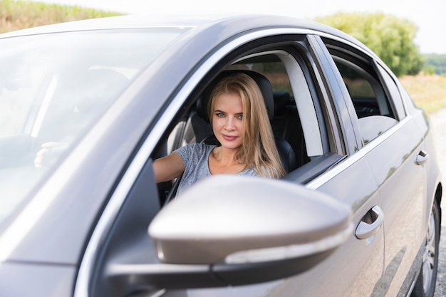 Jolie jeune femme conduisant une voiture Photo gratuit