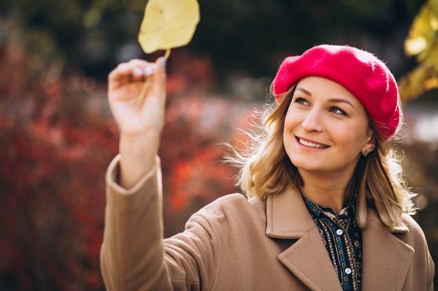 Jolie jeune femme dans un barret rouge à l'extérieur dans le parc Photo gratuit
