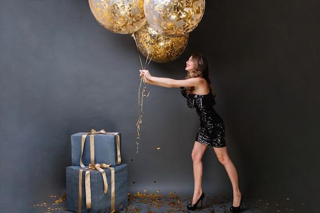 Jolie Jeune Femme Joyeuse En Robe De Luxe Noire S'amusant Avec De Gros Ballons Pleins De Guirlandes Dorées. Joyeux Anniversaire, Cadeaux, Souriant, Exprimant La Positivité. Photo gratuit