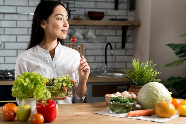 Jolie jeune femme mangeant une tomate cerise rouge tenant un bol de salade mixte Photo gratuit
