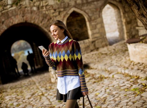 Jolie jeune femme marchant dans un parc en automne et utilisant un téléphone portable Photo Premium