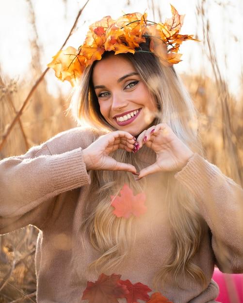 Jolie jeune femme portant des feuilles d'érable diadème en forme de coeur avec la main Photo gratuit