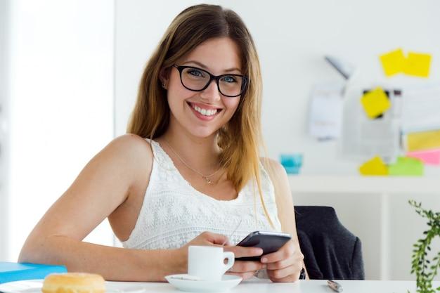 Jolie jeune femme qui utilise son téléphone mobile à la maison. Photo gratuit