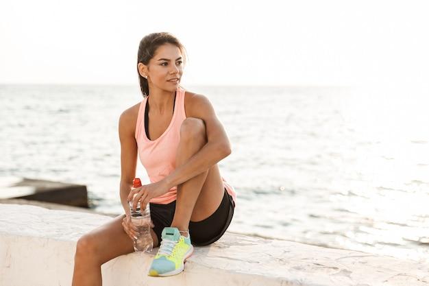 Jolie Jeune Femme De Remise En Forme Au Repos à La Plage Après Le Jogging, Tenant Une Bouteille D'eau Photo Premium