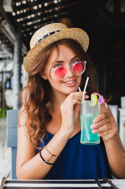 Jolie Jeune Femme En Robe Bleue Et Chapeau De Paille Portant Des Lunettes De Soleil Roses, Boire Des Cocktails D'alcool En Vacances Tropicales, Assis à Table Au Bar En Tenue De Style Estival, Souriant Heureux Dans L'ambiance De La Fête Photo gratuit