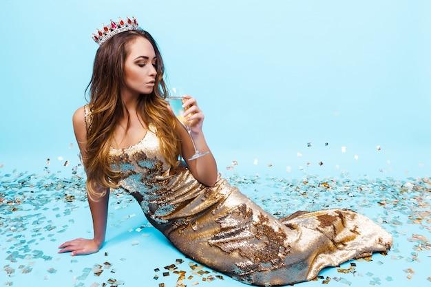Jolie jeune femme en robe d'or avec du champagne Photo Premium