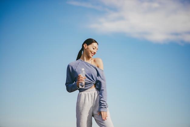 Jolie Jeune Femme S'entraînant Avec Une Bouteille D'eau Photo gratuit