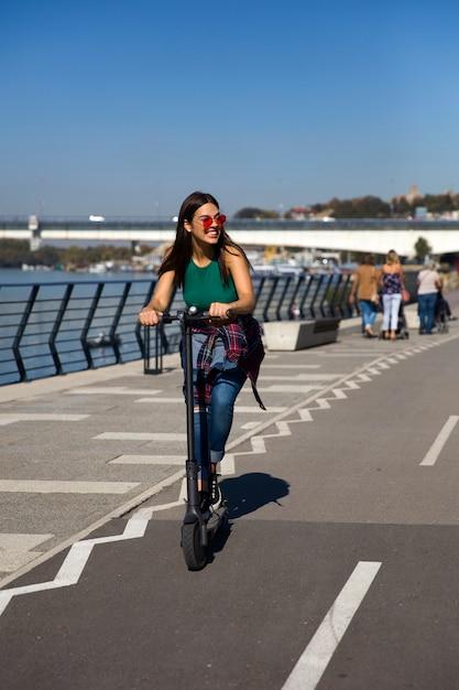 Jolie jeune femme sur un scooter électrique dans la rue Photo Premium