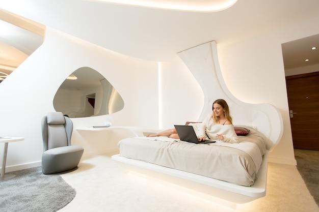 Jolie jeune femme se détendre sur un lit avec un ordinateur portable ...