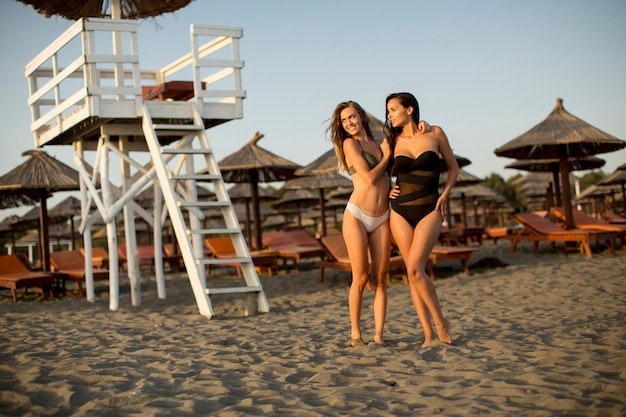 Jolie jeune femme se détendre sur la plage de sable Photo Premium