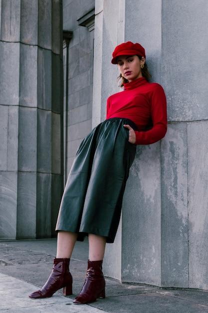 Une jolie jeune femme se penchant sur le mur avec les mains dans sa poche Photo gratuit