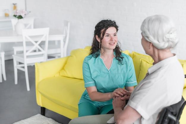 Une jolie jeune femme souriante donnant un soutien à une patiente âgée Photo gratuit
