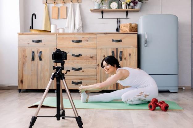 Jolie jeune femme souriante tourne une vidéo sur son entraînement sportif Photo Premium