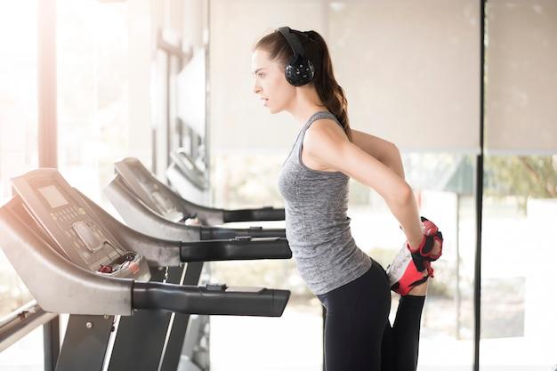 Jolie jeune femme sportive se réchauffe dans une salle de sport, mode de vie sain Photo Premium