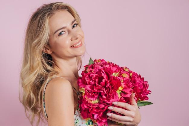 Une Jolie Jeune Femme Tenant De Belles Fleurs Rouges Sur Fond Rose Photo gratuit