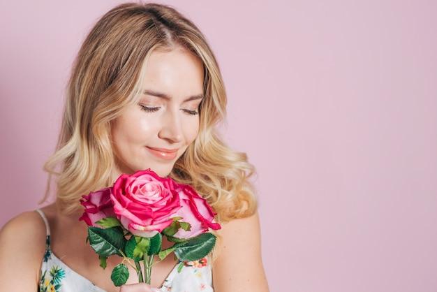 Jolie jeune femme tenant des roses roses dans la main sur fond rose Photo gratuit