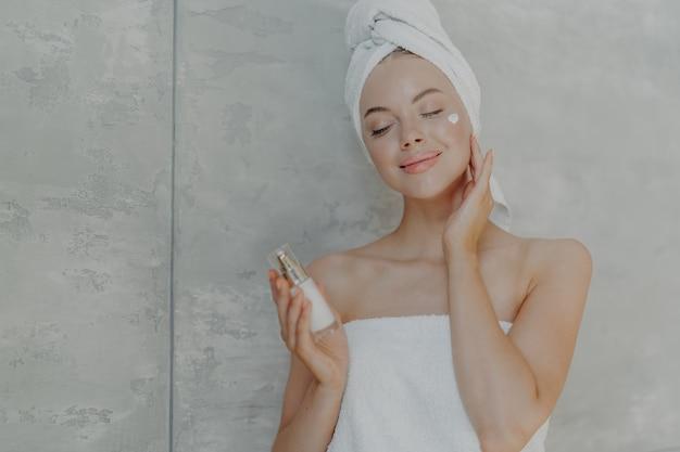 Jolie Jeune Femme Tient Une Bouteille De Lotion Pour Le Corps, Applique La Crème Pour Le Visage Sur Le Teint Photo Premium