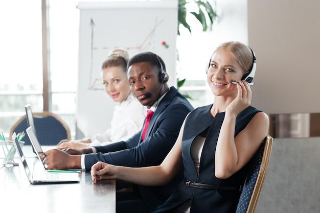 Jolie jeune femme travaillant dans un centre d'appels avec ses collègues Photo Premium